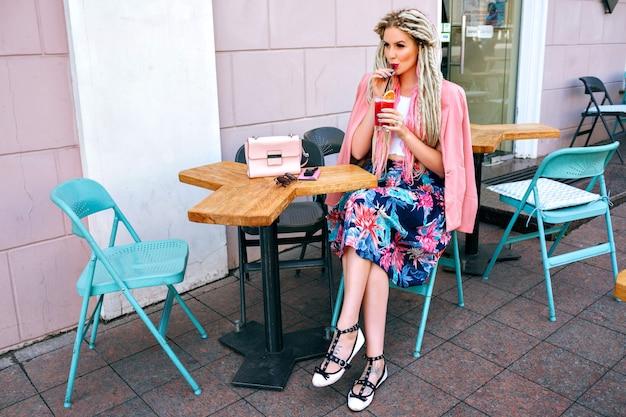 Mulher na moda na moda com roupas femininas elegantes, bebendo coquetel em restaurante