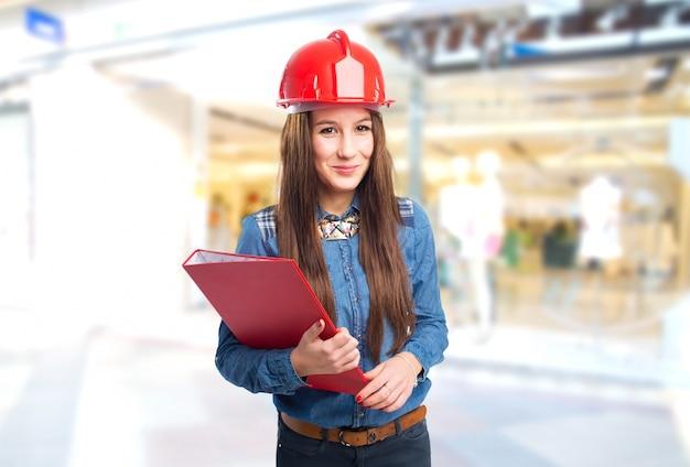 Mulher na moda vestindo um capacete vermelho e segurando uma pasta