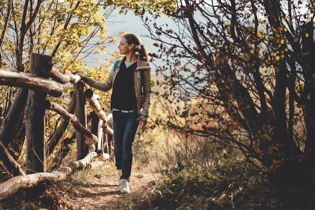 Mulher na montanha em pé ao lado da cerca e apreciando a vista