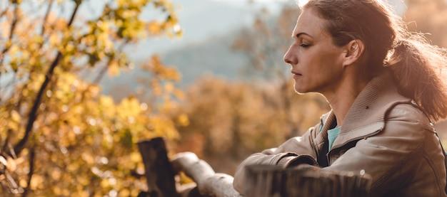 Mulher na montanha em pé em cima da muro com os olhos fechados