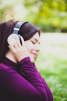 Mulher na música de escuta do parque com fones de ouvido.