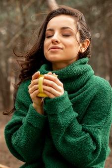 Mulher na natureza, desfrutando de chá
