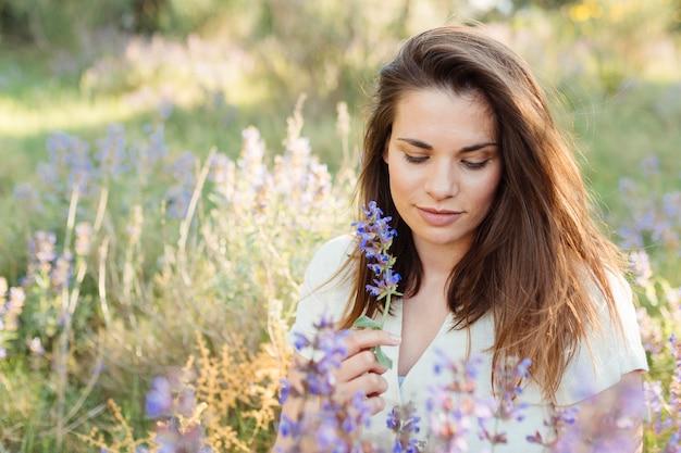 Mulher na natureza posando ao lado de lindas flores