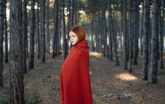 Mulher na natureza se cobriu com um cobertor vermelho no turismo de viagens na floresta