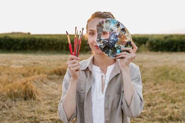 Mulher na natureza, segurando elementos de pintura