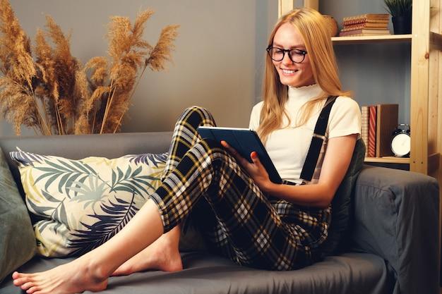 Mulher na noite em casa surfando na internet com tablet digital.