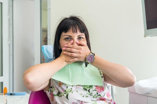 Mulher na odontologia fechando a boca com as mãos