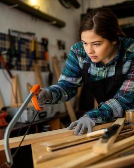 Mulher na oficina cortando prancha de madeira