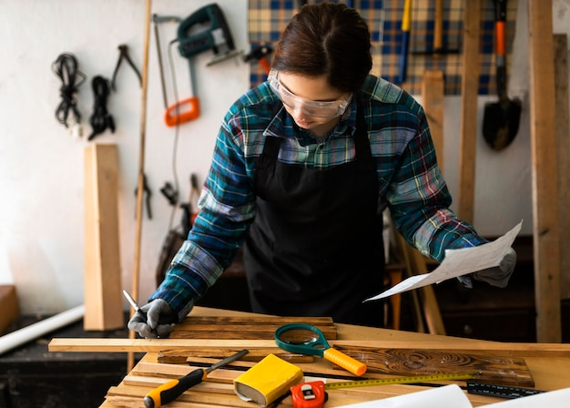 Mulher na oficina medida prancha de madeira