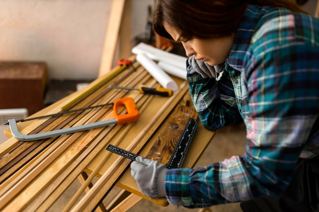 Mulher na oficina medindo madeira