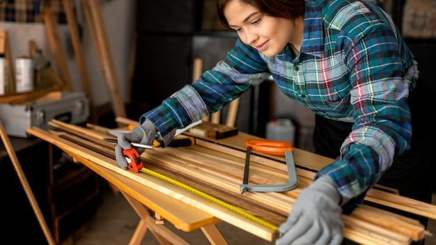 Mulher na oficina medindo prancha de madeira