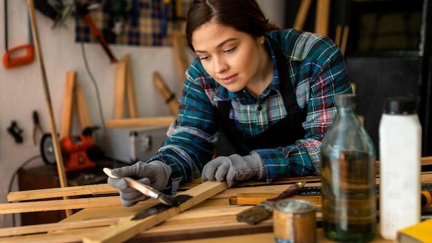 Mulher na oficina pintando prancha de madeira
