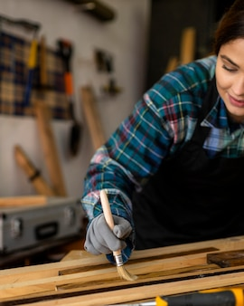 Mulher na oficina, tirando poeira de pranchas de madeira