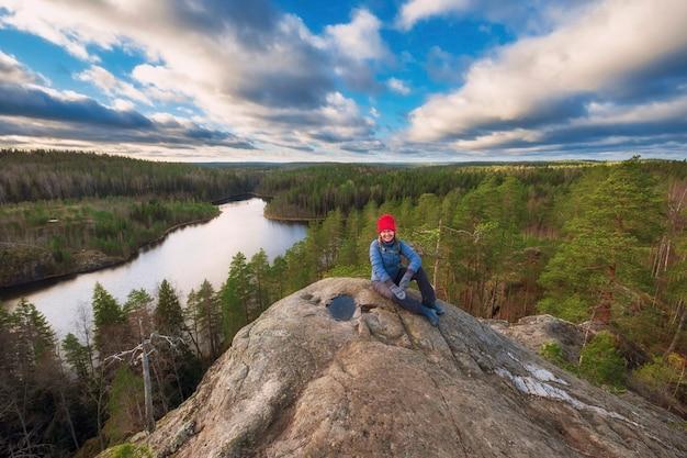 Mulher na paisagem do norte, lago azul entre a floresta verde spruce. a natureza do istmo da carélia e as rochas do lago triangular, vista do topo