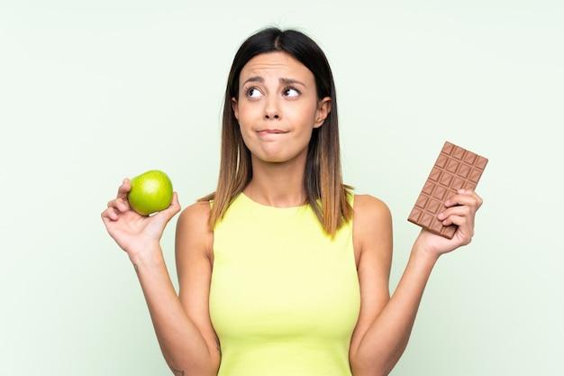 Mulher na parede verde, tendo dúvidas ao tomar uma tablete de chocolate em uma mão e uma maçã na outra