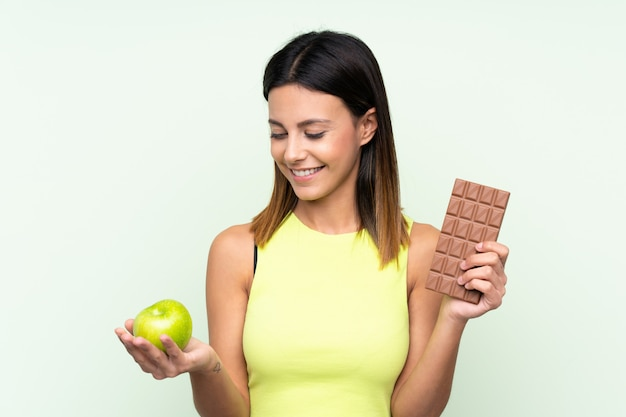 Mulher na parede verde, tomando uma tablete de chocolate em uma mão e uma maçã na outra