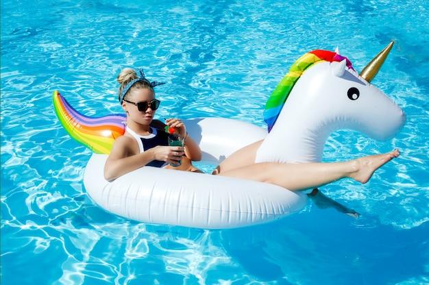 Mulher na piscina em um unicórnio inflável. o conceito de férias de verão e férias.