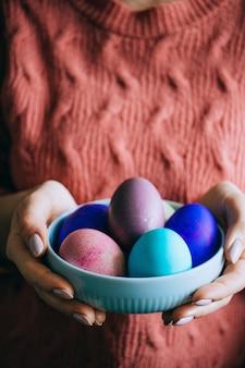 Mulher na placa de lã coral da posse da camiseta com ovos da páscoa coloridos. feliz páscoa