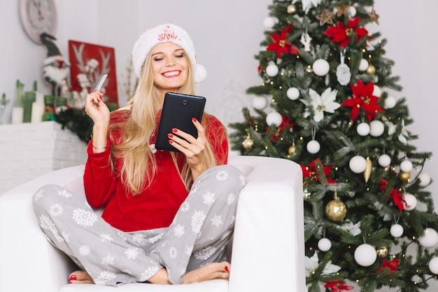 Mulher na poltrona com tablet e cartão