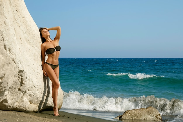 Mulher na praia ao lado de falésias brancas
