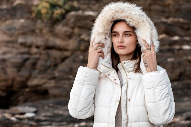 Mulher na praia com casaco de inverno