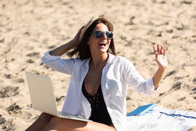 Mulher na praia com laptop