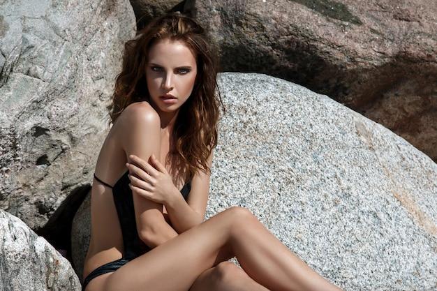 Mulher na praia com pedras