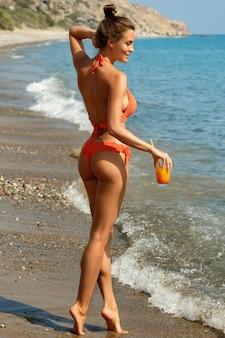 Mulher na praia com um copo de cocktail