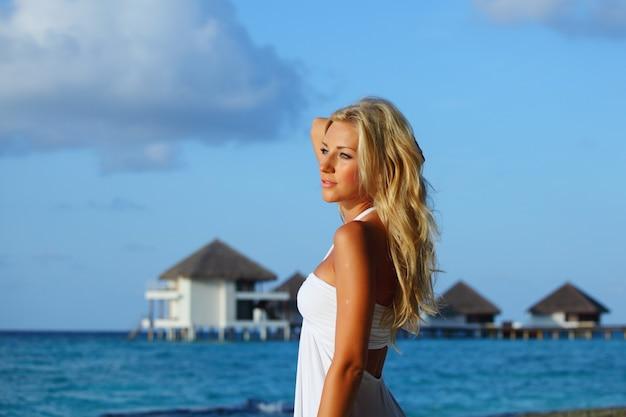 Mulher na praia com uma casa de praia tropical ao fundo