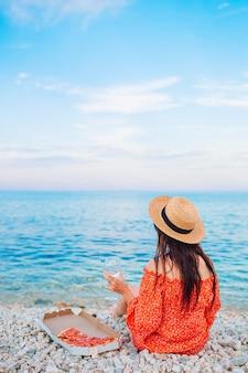 Mulher na praia fazendo piquenique com uma taça de vinho e pizza nas costas