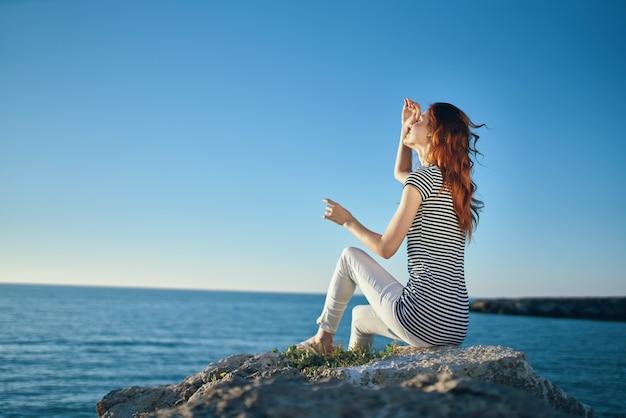 Mulher na praia nas montanhas, mar azul e nuvens vista superior cópia espaço