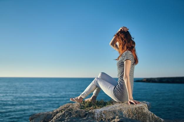 Mulher na praia nas montanhas, mar azul e nuvens