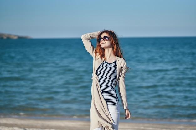 Mulher na praia no verão, perto do mar, com um casaco e uma camiseta