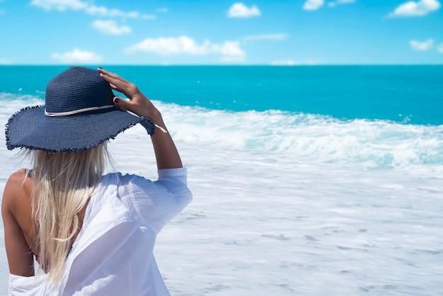 Mulher na praia, olhando para o mar, aproveitando as férias de verão
