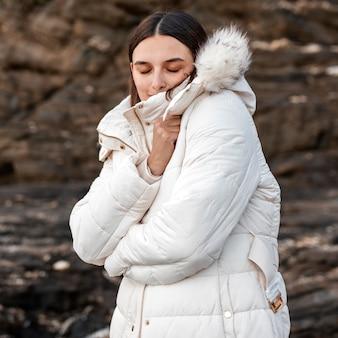 Mulher na praia sozinha com jaqueta de inverno