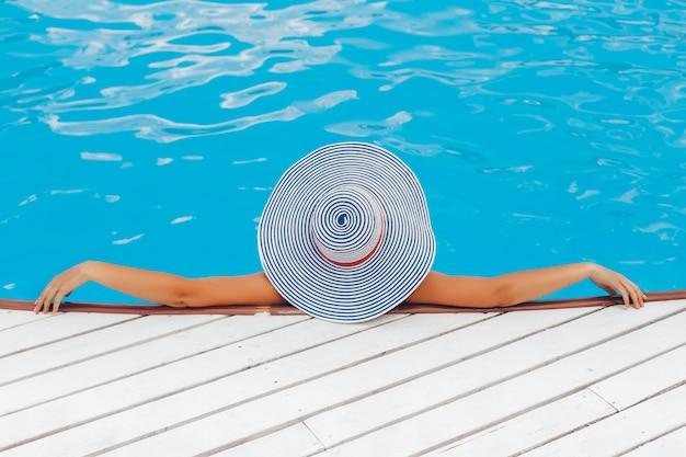 Mulher na praia sozinha relaxando em um chapéu. verão. ao ar livre. copie o espaço. conceito