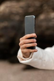Mulher na praia tirando fotos com smartphone