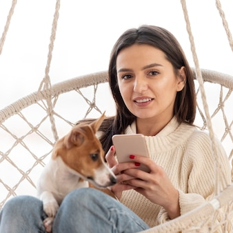 Mulher na rede com seu cachorro e smartphone