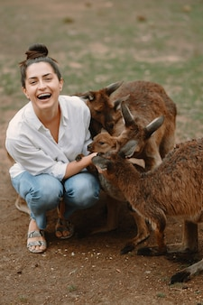 Mulher na reserva está brincando com um canguru