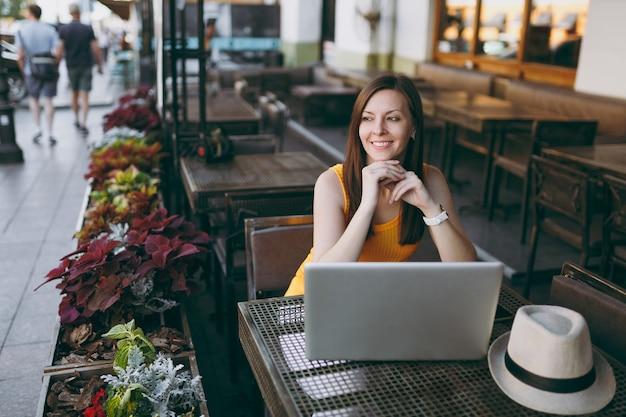 Mulher na rua ao ar livre, café, café, sentada à mesa, trabalhando em um moderno laptop, relaxando no restaurante durante o tempo livre