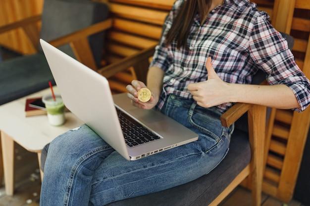 Mulher na rua ao ar livre, café, café, sentada com o computador laptop pc, segura bitcoin, moeda de metal dourada