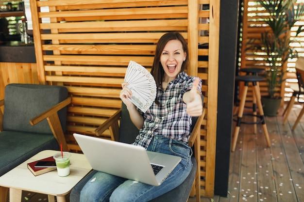 Mulher na rua ao ar livre, café, café, sentada com um computador laptop moderno, segurando um monte de notas de dólares, dinheiro em espécie