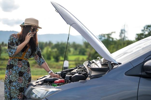 Mulher na rua com carro quebrado, pedindo ajuda