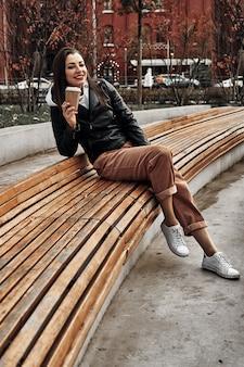 Mulher na rua com um copo de papel descartável. leve comida, caminhe pela cidade.