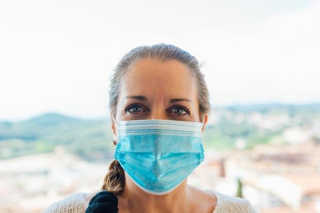 Mulher na rua com uma máscara de proteção