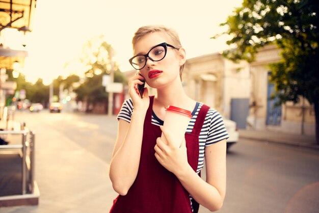 Mulher na rua falando ao telefone com uma xícara de café a pé