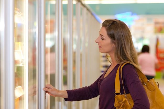 Mulher na seção de freezer de supermercado