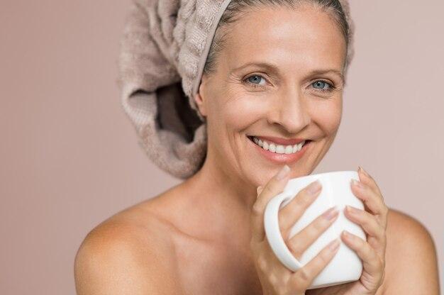Mulher na toalha bebendo infusão