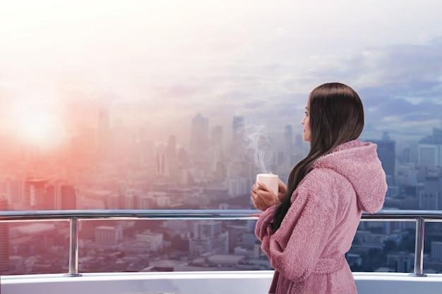Mulher na varanda com uma xícara quente nas mãos, apreciando a vista da cidade