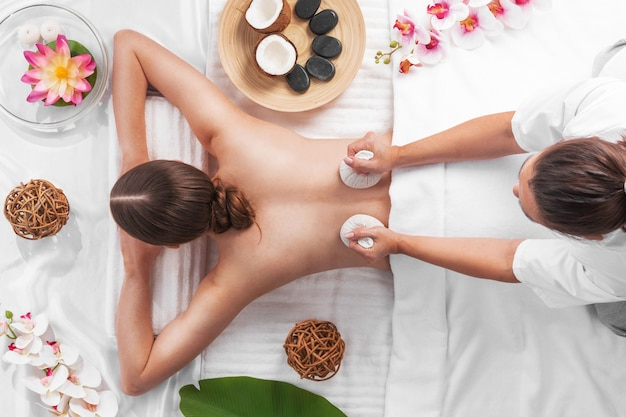 Mulher na vista de reboque de massagem tailandesa spa, conceito de tratamentos de beleza. orquídea e flores de lótus, pedras de coco e bolsas de ervas